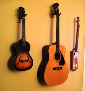 A ukulele, guitar and cigar box guitar, hanging on the wall